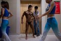 An amateur bodybuilder is covered in bronze paint