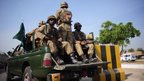 Pakistani troops ride to areas affected by an earthquake in military trucks in Karachi on September 25, 2013.