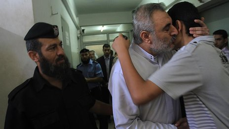 Fathi Ashram (centre) hugs his son