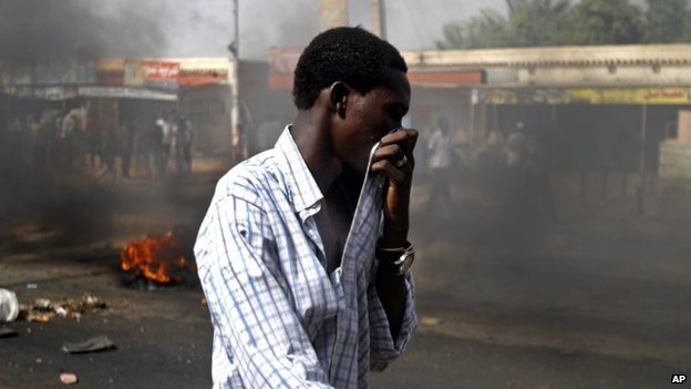 A Sudanese man covers his mouth from heavy smoke after protesters burnt tyres to close the highway to northern cities amid a wave of unrest over the lifting of fuel subsidies by the Sudanese government, in Kadro, 15 miles (24.14 kilometres) north of downtown Khartoum, Wednesday, 25 September, 2013.