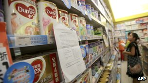 A Chinese consumer looking at baby milk formula in a store in China