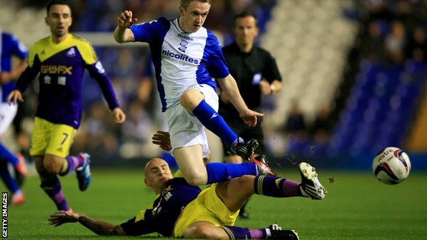 Jonjo Shelvey of Swansea City tackles Shane Ferguson of Birmingham City during the Capital One Cup Third Round match