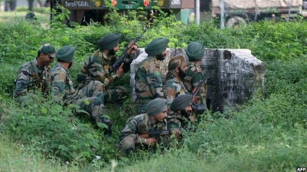 Indian army soldiers gather behind a small wall during an attack by militants on an army camp at Mesar in Samba District, some 20kms south-east of Jammu on September 26, 2013