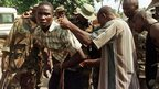A Sierra Leone civilian is searched by West African peacekeepers part of ECOMOG forces at a gas station in Freetown, Sierra Leone to determine if he is a rebel fighter, 10 January 1999