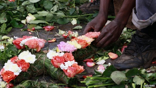 A trader prepares flowers in the shape of a cross for sale outside the City Mortuary in Nairobi