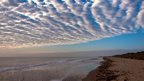Patterned cloud, shaped in rows over a sandy beach. Blue sky in the distance.