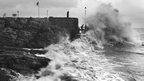 A black and white photo of waves crashing into a sea wall. People standing at the edge, about to get hit by a huge wave.