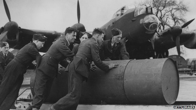 A ground crew move a 4,000 pound blast bomb into position for loading onto a Lancaster bomber, 18 October 1943