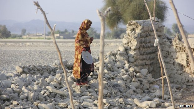 A survivor walks on the rubble of a mud house which collapsed following the quake in the town of Awaran, southwestern Pakistan, 27 September 2013