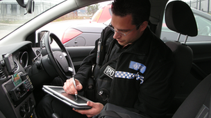 An officer records information on a TETRATAB device
