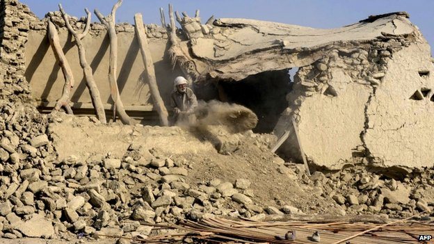 A Pakistani earthquake survivor clears debris from his collapsed mud house in the Dhall Bedi Peerander area of the earthquake-devastated district of Awaran on 27 September 2013