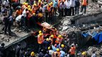Rescue workers use a stretcher to carry a woman who was rescued from the rubble at the site of a collapsed residential building in Mumbai.