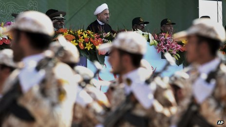 Iran's President Hassan Rouhani, centre, reviews military forces marching during an annual military parade in Tehran, Iran, on 22 September 2013