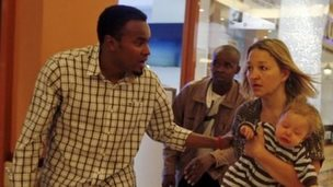 Abdul Haji leads a woman and child to safety