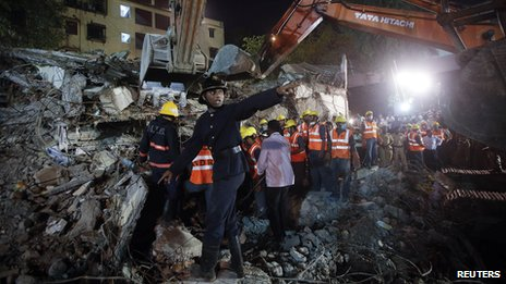 A rescue worker calls for a stretcher as others search for survivors at the site of a collapsed residential building in Mumbai