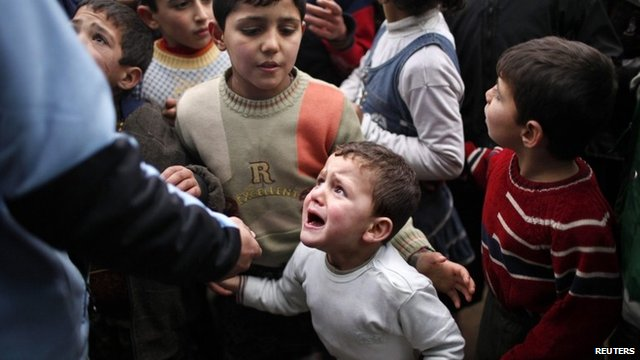 A Syrian child refugee cries as he stands at a queue waiting to receive aid from Turkish humanitarian agencies at Bab al-Salam refugee camp in Syria