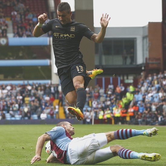 Manchester City's Kolarov jumps over Aston Villa's Vlaar