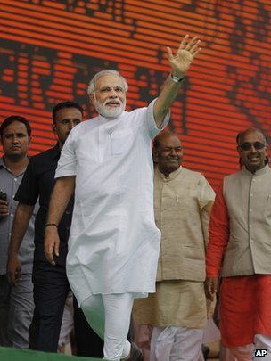 India's opposition Bharatiya Janata party (BJP) leader Narendra Modi waves to supporters as he arrives to address a public rally in New Delhi, India, Sunday, Sept. 29, 2013.