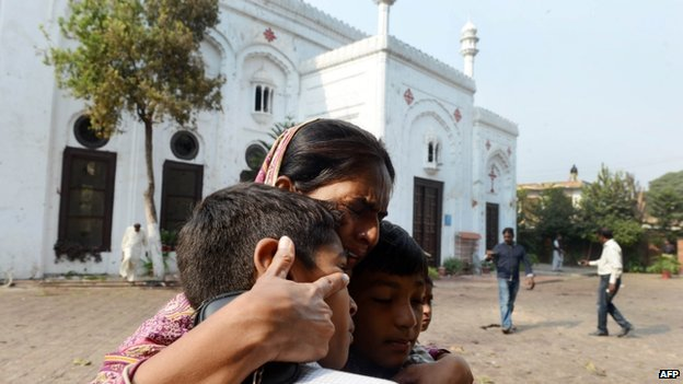 A Pakistani Christian woman embraces children as she mourns the death of relatives at the suicide bombing site at All Saints church in Peshawar on September 23, 2013