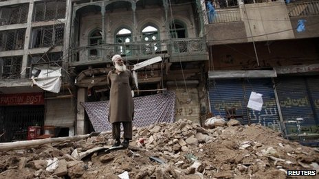 A man stands on a pile of rubble in front of a damaged building after it was hit by a bomb blast, which happened on Sunday, in Peshawar September 30, 2013.