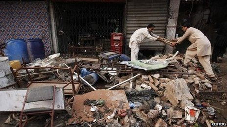 Men collect their belongings from the debris of a damaged building after it was hit by a bomb blast, which happened on Sunday, in Peshawar September 30, 2013