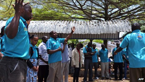 Nakumatt supermarkets' staff members, who survived the four-day siege, pray on  for the victims outside the Westgate mall on 29 September 2013