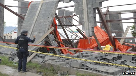 A federal police officer takes a photograph at the collapsed Santa Clara Catholic Church on 29 September, 2013