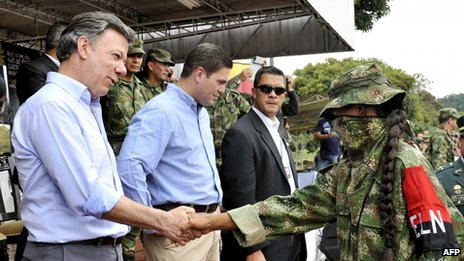 Colombian President Juan Manuel Santos (left) shakes hands with a member of the ELN guerrilla who has defected at a military base on 16 July 2013