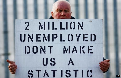 "A man holding a sign saying ""2 million unemployed - don't make us a statistic"""
