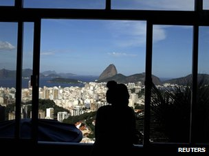 Woman looks out window over Rio