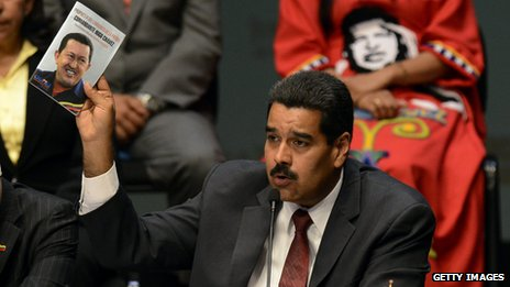 Mr Maduro holds up a booklet with a picture of Mr Chavez at the ministers' swearing-in ceremony in Caracas on 22 April 2013