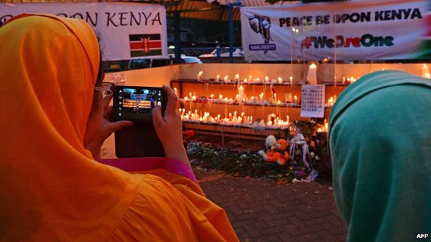 A woman takes a picture of candles outside the Westgate Mall on Sunday in Nairobi