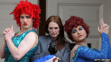 Julianne Moore with drag artists in red wigs