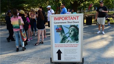 Tourists walk by a sign announcing that the Statue of Liberty is closed