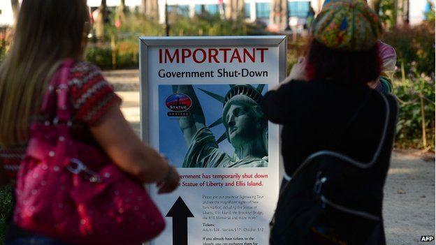 Tourists look at a sign announcing that the Statue of Liberty is closed due to a US government shutdown in New York, on 1 October 2013.