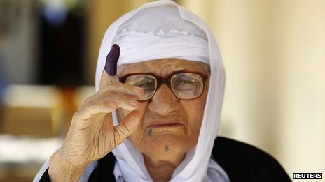 A woman shows her ink-dyed finger after voting