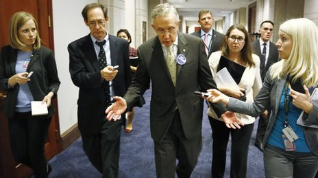 US Senate Democratic Leader Harry Reid (C) is trailed by reporters as he departs a rally celebrating the start of the Affordable Care Act at the US Capitol 1 October 2013