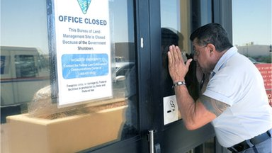 US Post Office letter carrier Jacob Ribald peeks into the window of the Bureau of Land Management office in Las Cruces, NM 1 October 2013