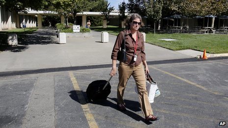 With her rolling backpack and bags in hand, Bronwyn Hogan, an employee of the US Fish and Wildlife Service, leaves the federal offices in Sacramento, California 1 October 2013