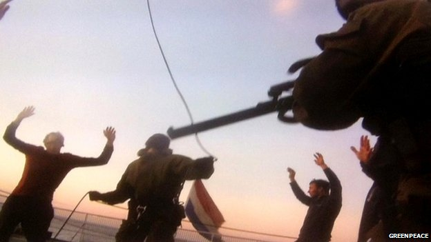 A handout picture taken with camera phone off a computer screen in the Pechora Sea on 19 September 2013, and provided by Greenpeace International shows Russian security forces officers standing on the deck of Greenpeace's Arctic Sunrise.