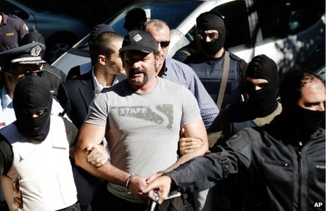 Golden Dawn MP Ioannis Lagos is led away by police from court in Athens, 2 October