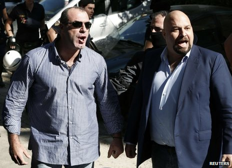 Golden Dawn MPs Ilias Panagiotaros (R) and Nikos Michos shout at media outside court in Athens, 2 October