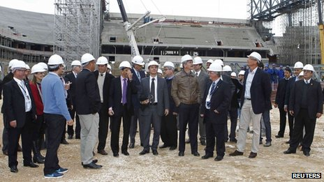 Jerome Valcke (5th from right) and Brazil's Sports Minister Aldo Rebelo (centre in brown jacket) tour the construction site of the Arena da Baixada stadium
