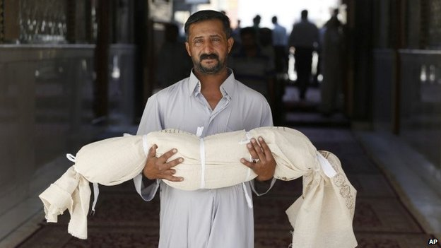 A man carries the body of his five-year-old son, who was killed in a bombing in Najaf, Iraq (14 September 2013)