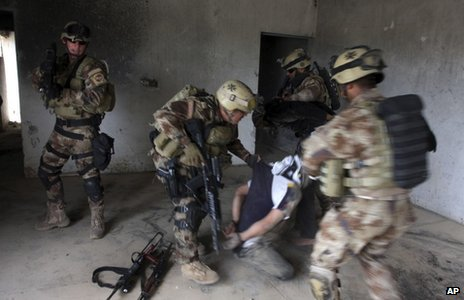 Iraqi soldiers detain a suspected militant in Latifiya (16 March 2013)
