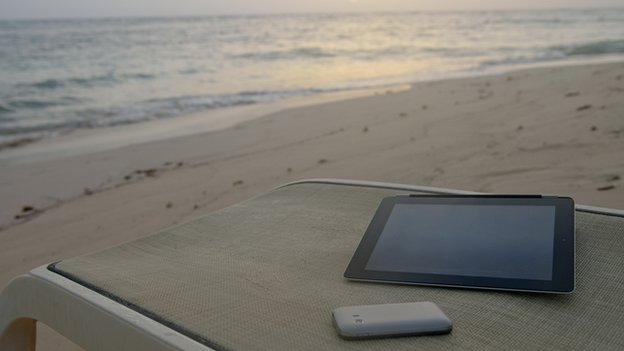 A smartphone and tablet on a beach