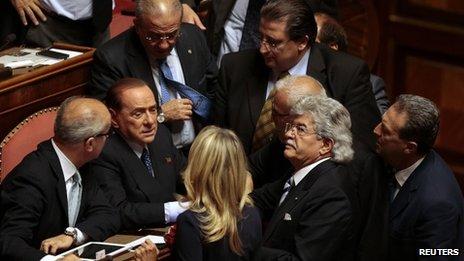 Silvio Berlusconi (2L) talks with senators after Prime Minister Enrico Letta's speech