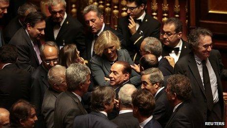 Silvio Berlusconi (C) leaves during a confidence vote at the Senate in Rome