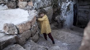A displaced Syrian girl walks upstairs from her family cave dwelling near Kafer Rouma, in ancient ruins used as temporary shelter by those families who have fled from the heavy fighting and shelling in the Idlib province countryside of Syria, on 27 September 2013