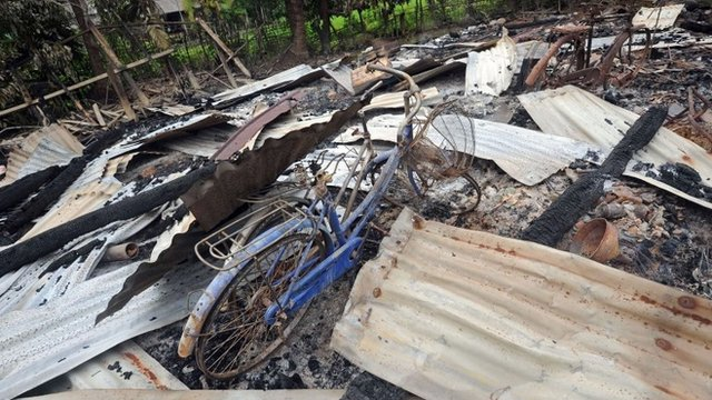 A bicycle stands in the ruins of a house